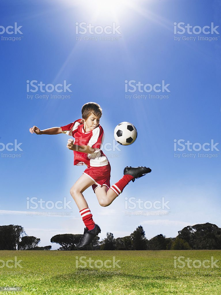 Young boy in uniform kicking soccer ball stock photo