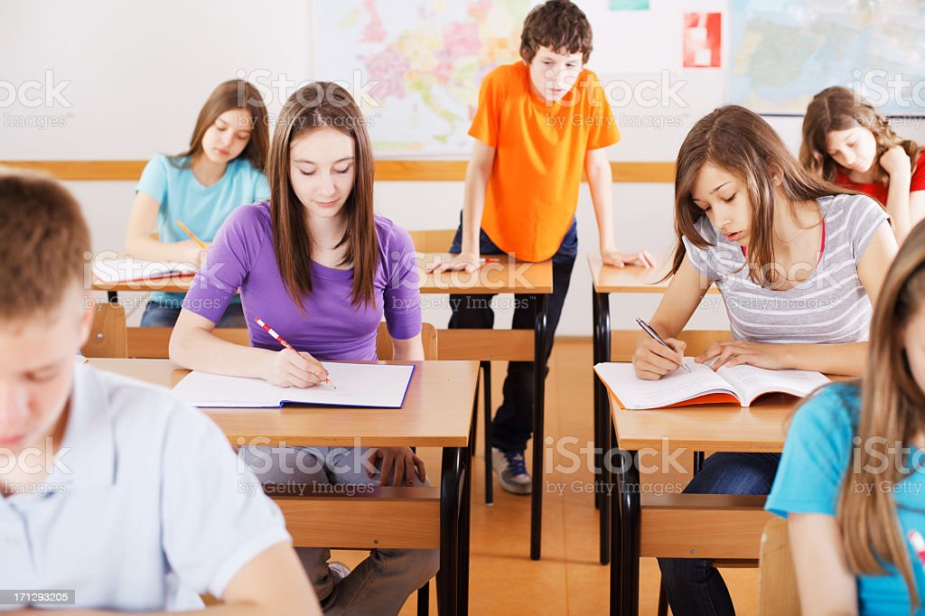 Young boy is copying the assignment on class stock photo
