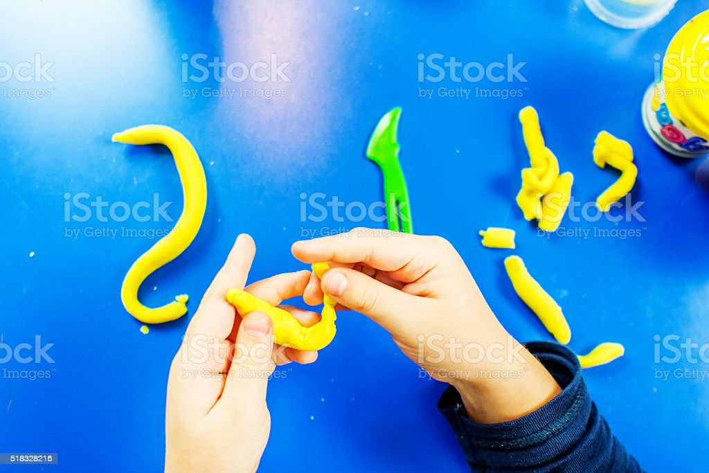 young boy is playing with plasticine stock photo