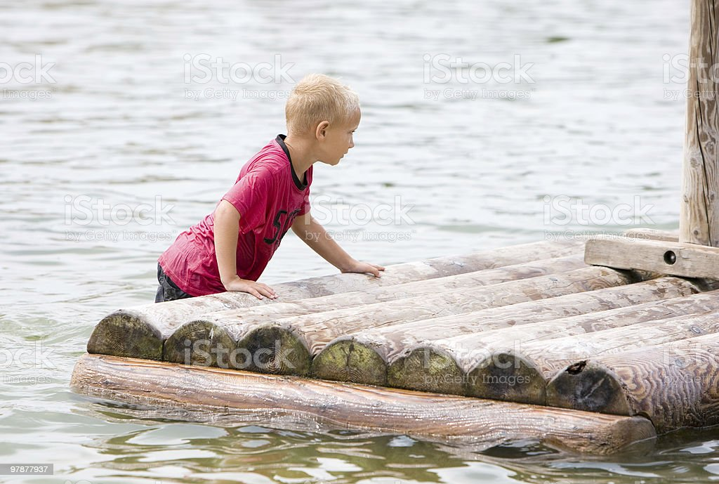 Young boy is pushing his raft stock photo