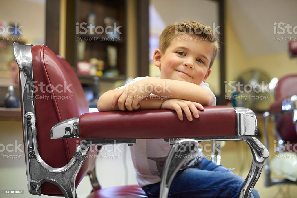 Young boy is very happy with his new haircut stock photo