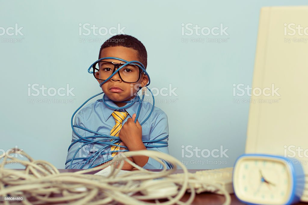 Young Boy IT Professional Frowns at Computer with Wire stock photo