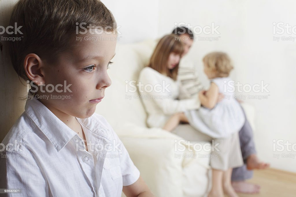 Young boy jealous of his younger sister stock photo