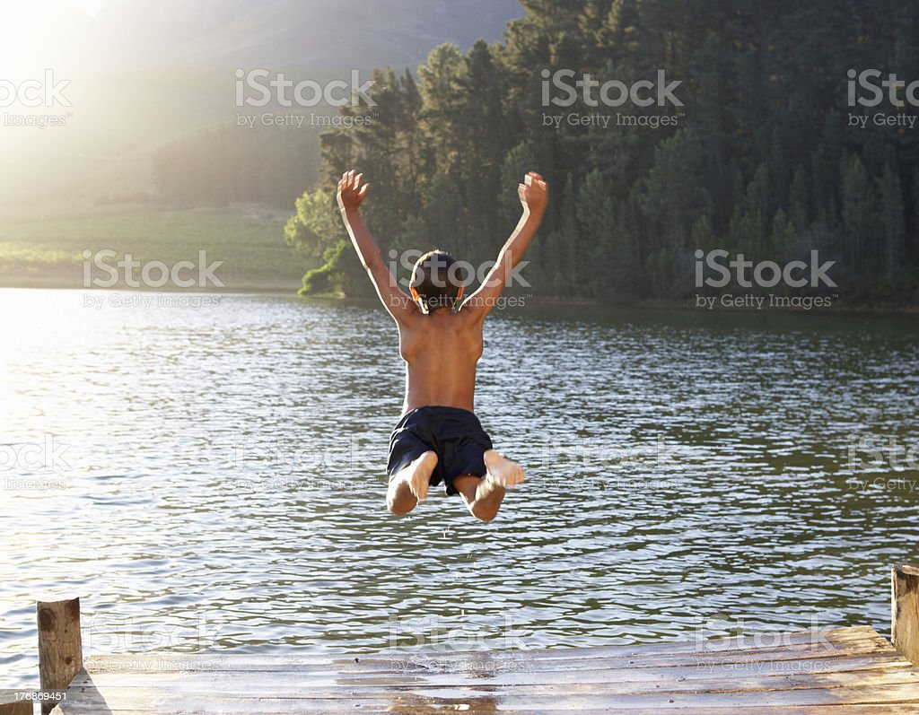 Young boy jumping into lake stock photo