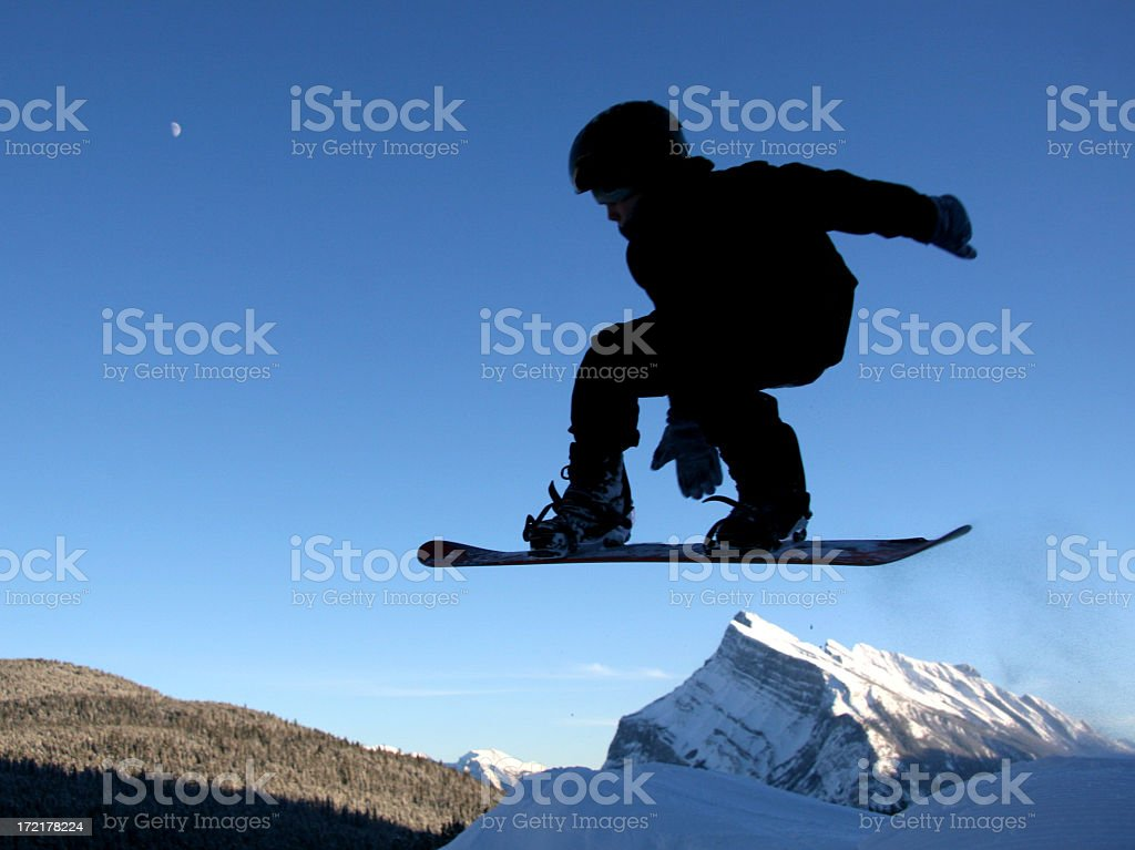 Young Boy Jumping on Snowboard in the Canadian Rockies stock photo