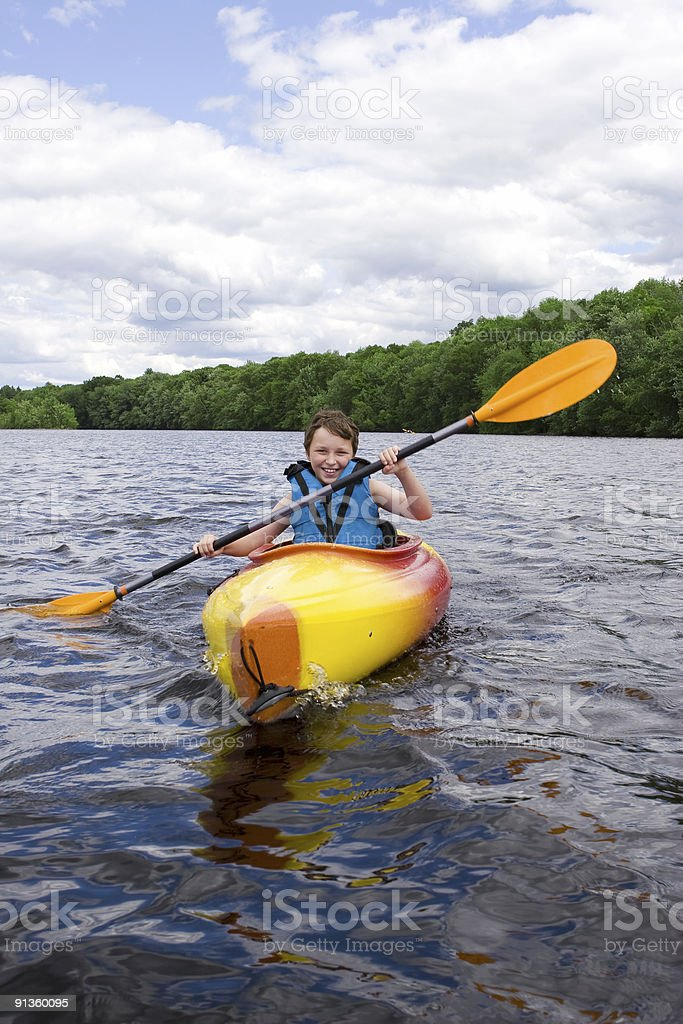 A young boy kayaking in a big lake royalty-free stock photo