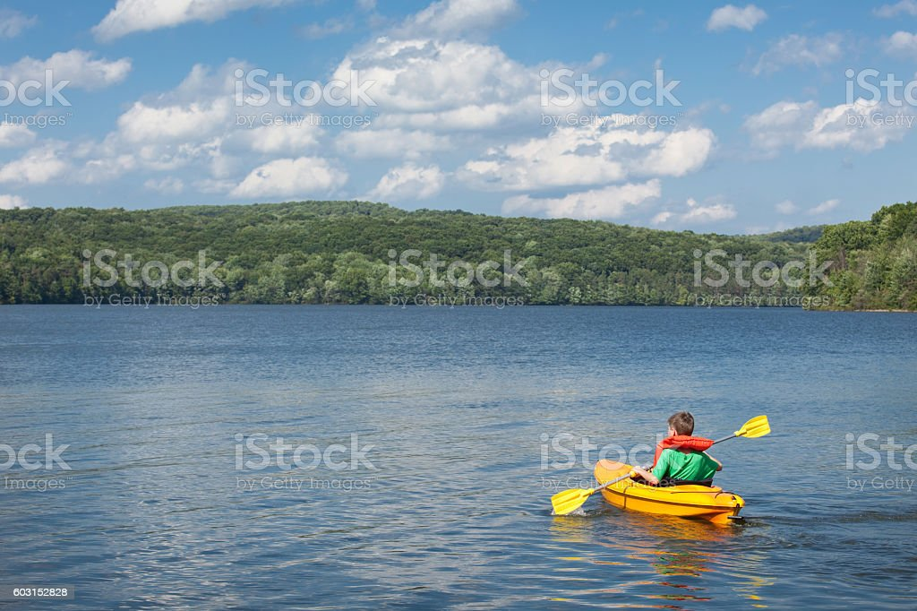 Young Boy Kayaking On Beautiful Lake stock photo
