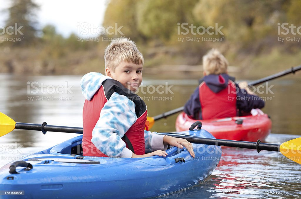 Young boy kayaking turning back to look at the camera royalty-free stock photo