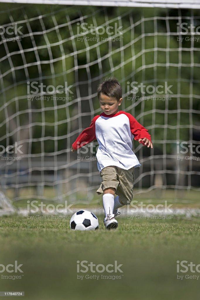 Young Boy Kicking A Soccer Ball royalty-free stock photo