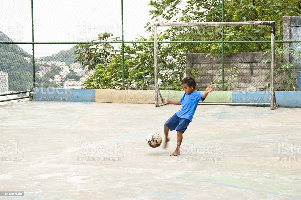 Young Boy Kicking Ball, Rio de Janeiro, Brazil, South America. royalty-free stock photo