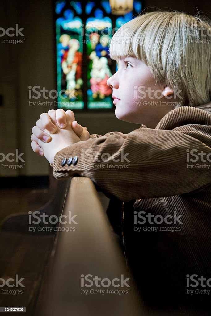 Young Boy Kneeling and Praying in Church stock photo