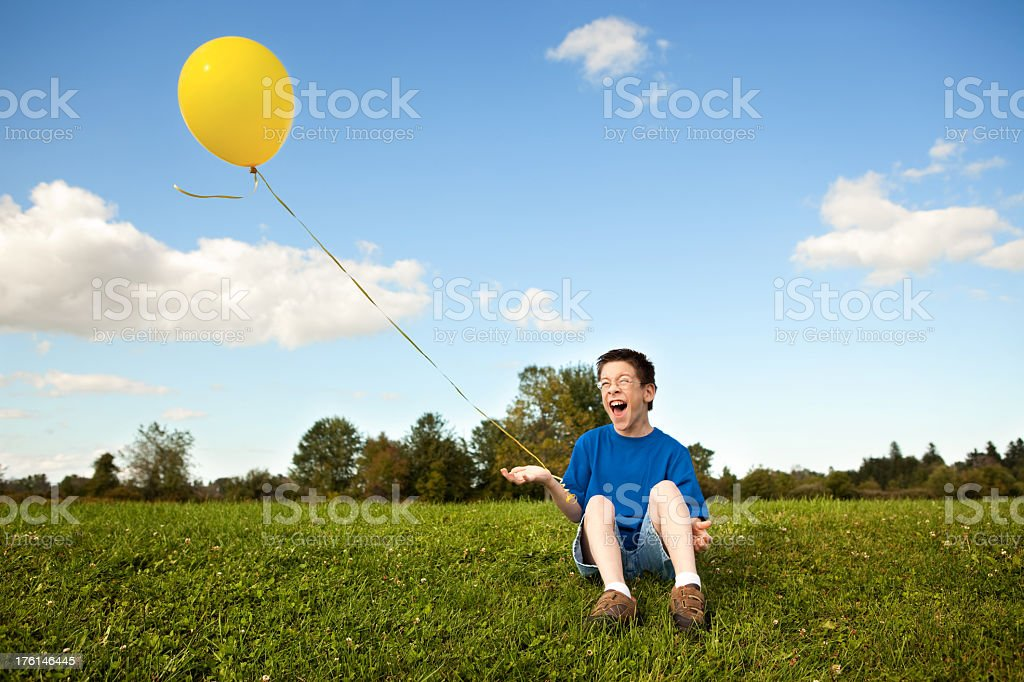 Young Boy Laughing and Holding a Balloon Outside royalty-free stock photo
