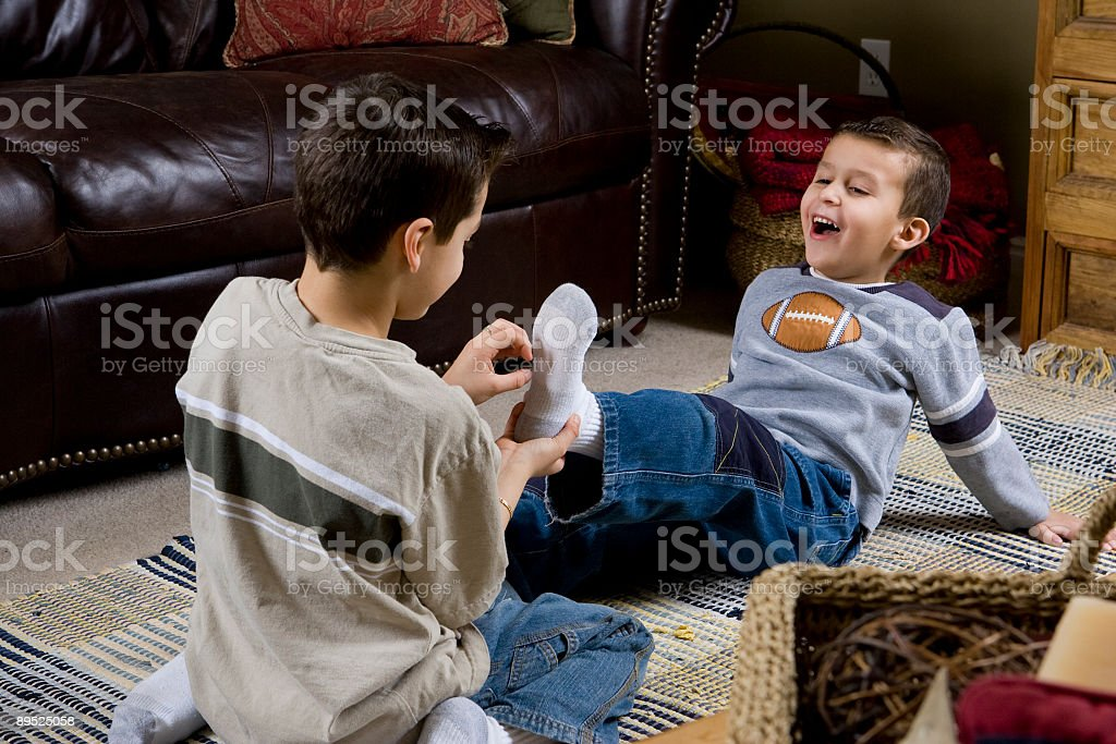 Young boy laughing at tickled feet, shallow focus royalty-free stock photo