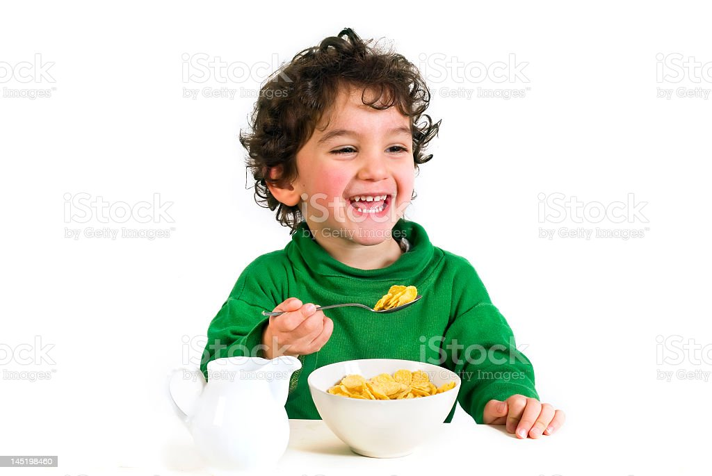 Young boy laughing, enjoying his morning cereal with milk stock photo