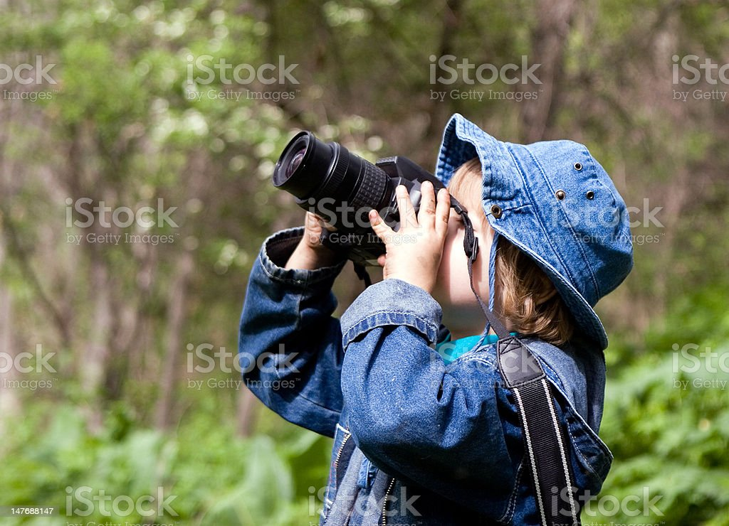 Young boy learning photography in the outdoors royalty-free stock photo