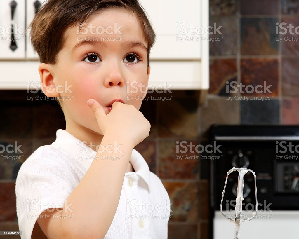Young boy licking icing royalty-free stock photo