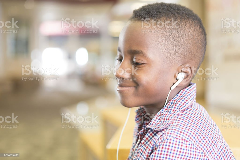 Young boy listening with headphones at school royalty-free stock photo