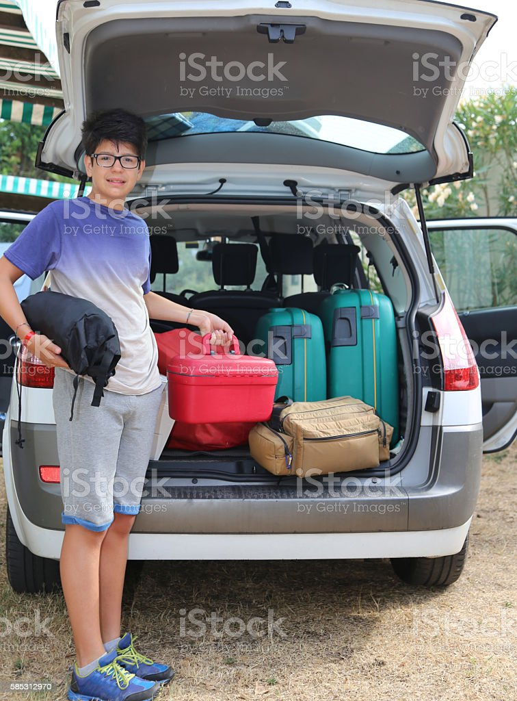 young boy loaded the trunk of the car before departure stock photo