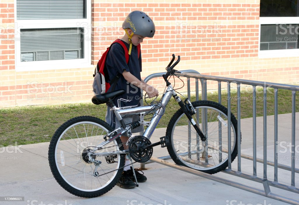 Young boy locks up his silver bike before going to school  stock photo