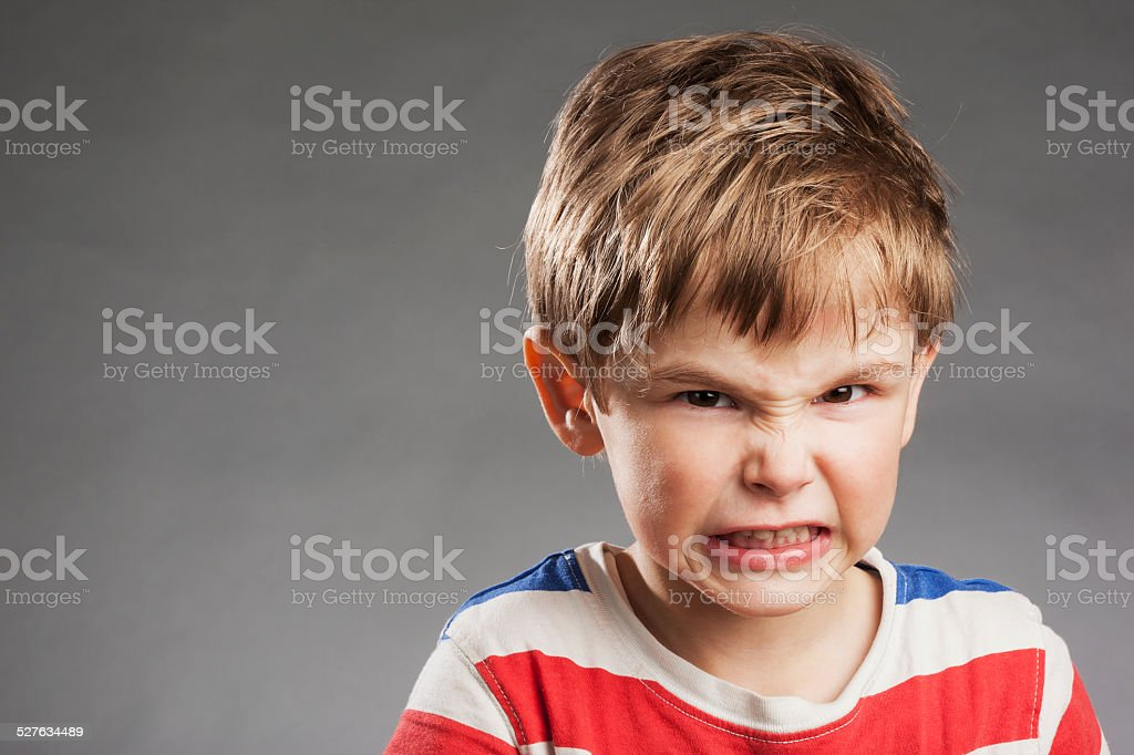 Young boy looking angry, clenching teeth against gray background stock photo