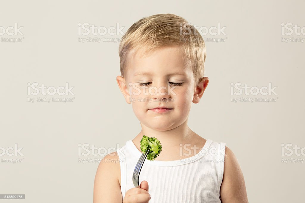 Young Boy Looking at Broccoli on His Fork stock photo