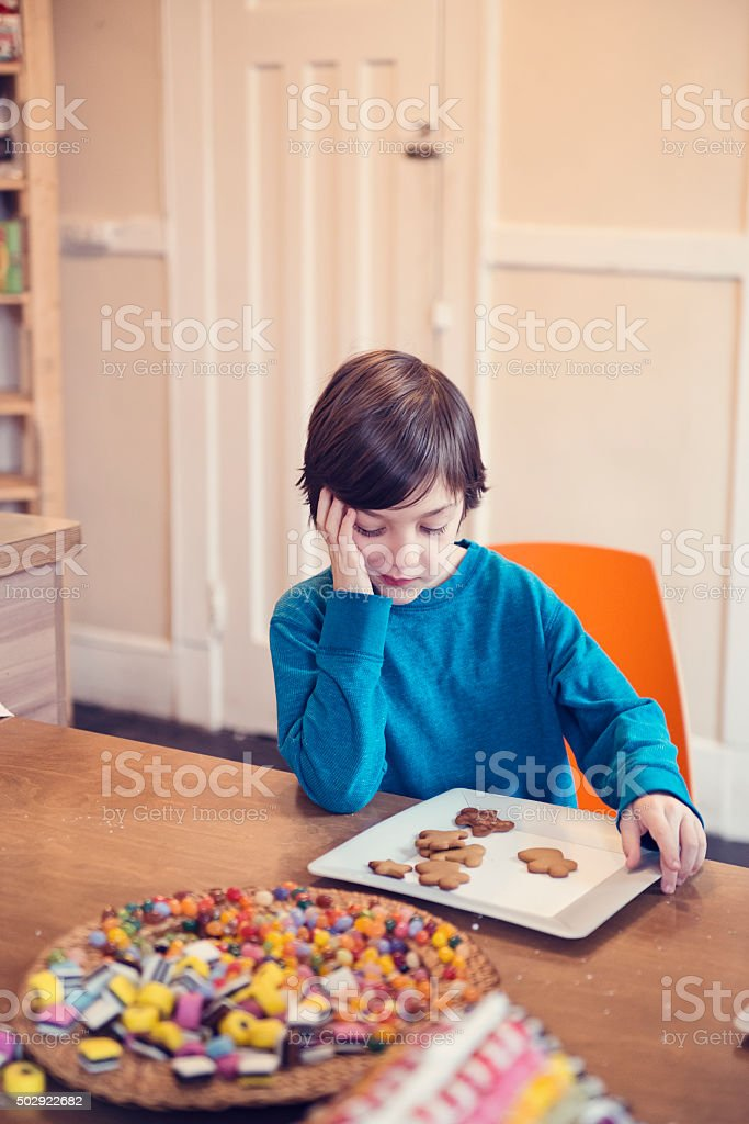Young boy looking at gingerbread cookies with expressive face. stock photo