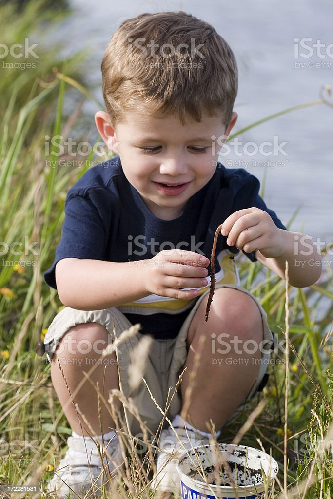 Young boy looking at worm crouching stock photo