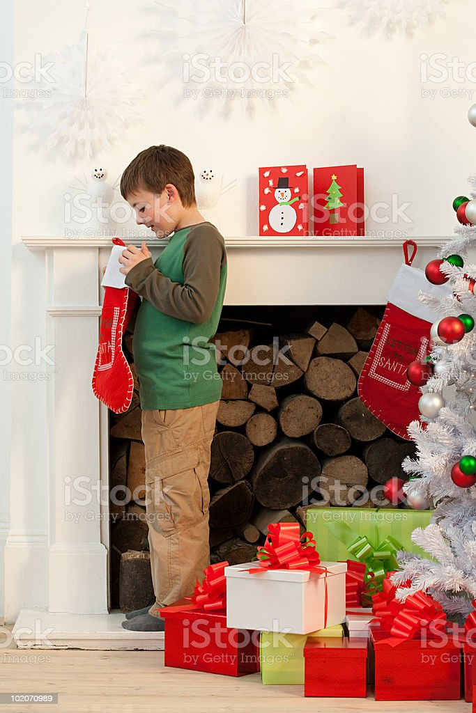Young boy looking in Christmas stocking royalty-free stock photo