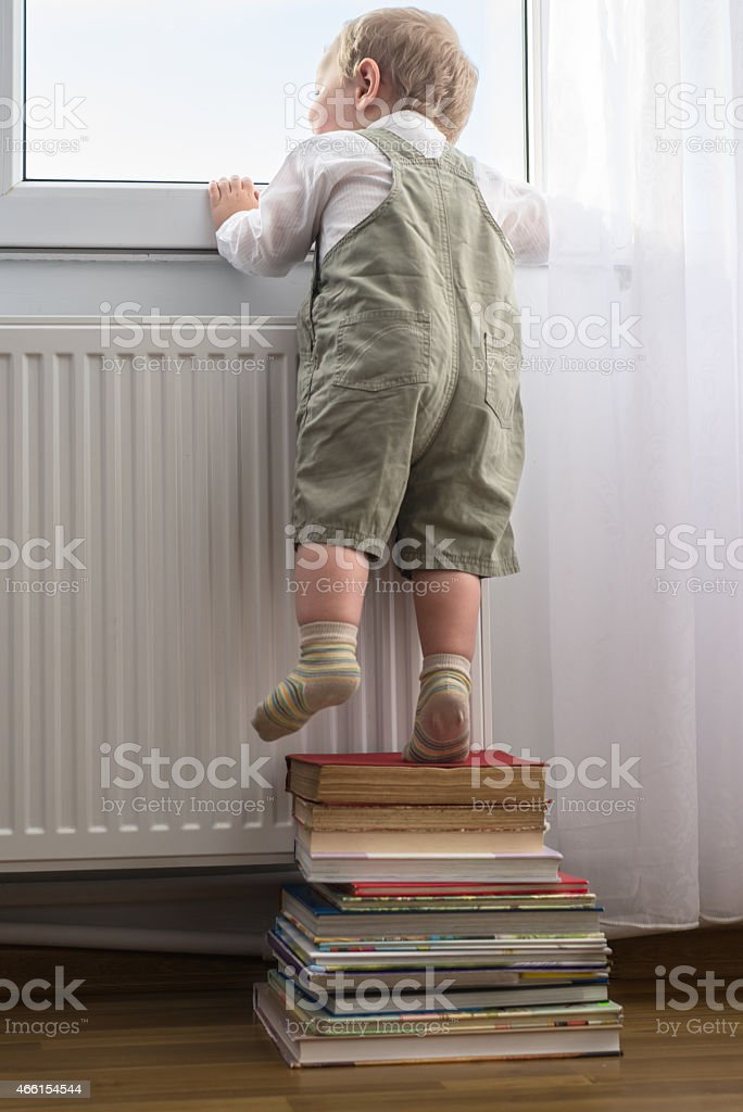 Young boy looking outside the window stock photo