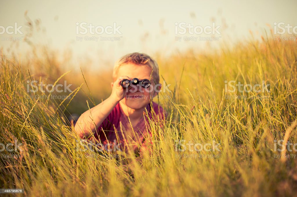 Young Boy Looking Through Binoculars Hiding in Grass stock photo