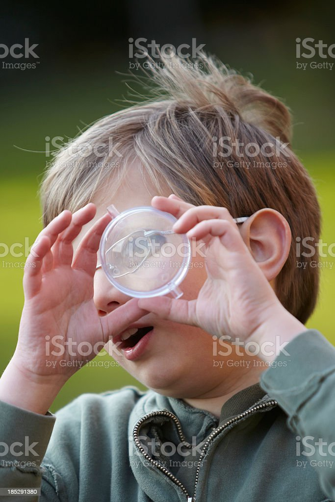 Young boy looking through magnifying glass royalty-free stock photo