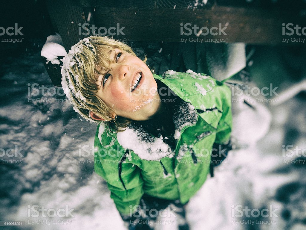 Young boy looks up, watches snow fall stock photo