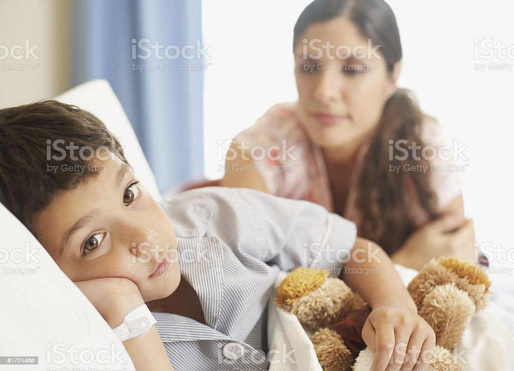 Young boy lying in hospital bed with teddy bear and woman looking over him royalty-free stock photo