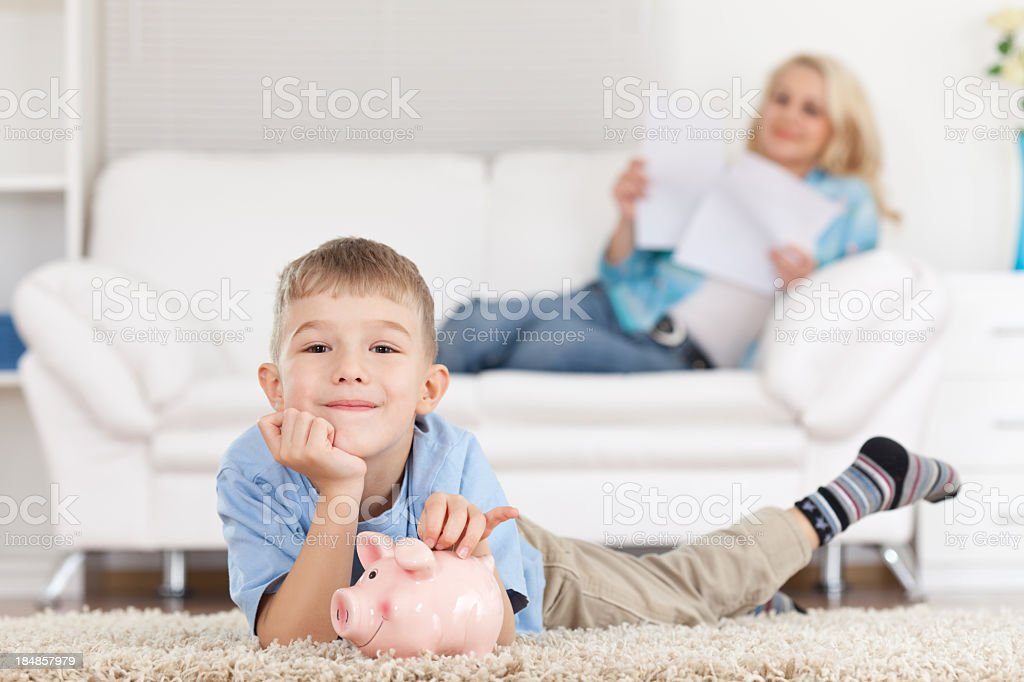 Young boy lying on a carpet with a piggy bank royalty-free stock photo