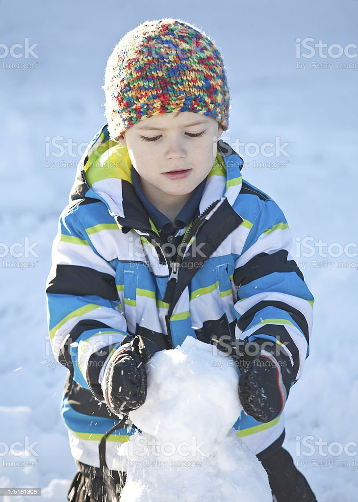 Young Boy Making A Snowman royalty-free stock photo