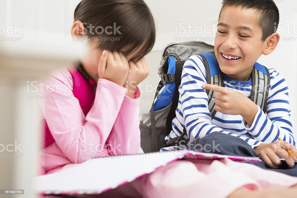 Young boy making fun of his younger sister stock photo
