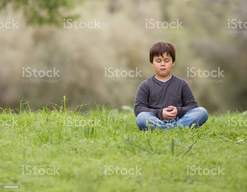 young boy meditating zen like in  nature stock photo