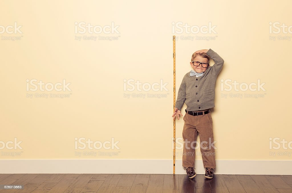 Young Boy Nerd Measures Height and is Tall stock photo