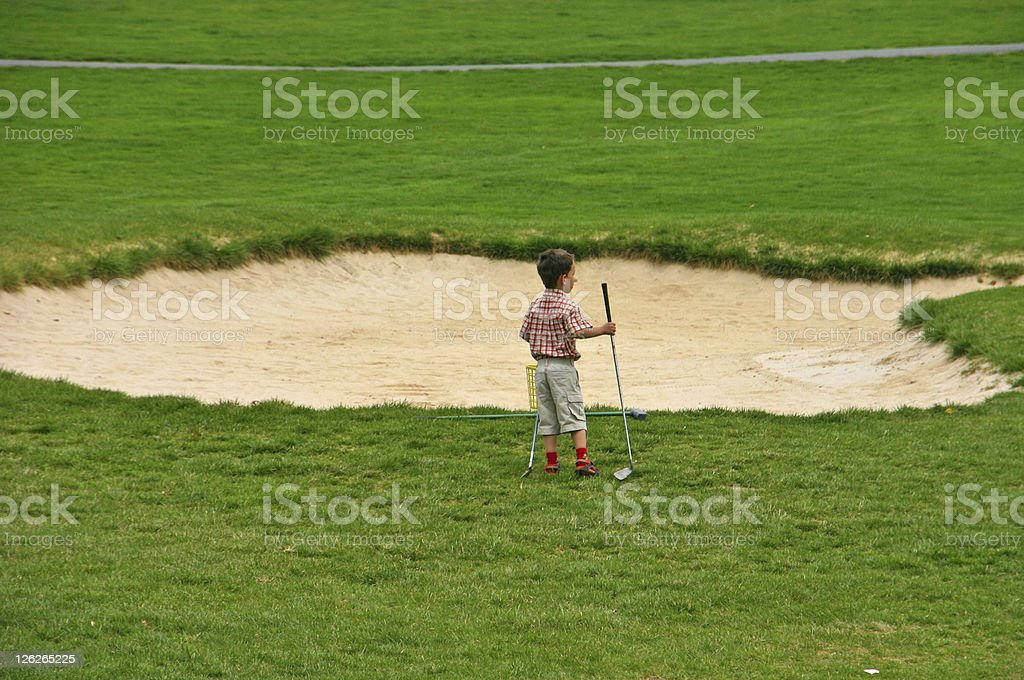 Young boy on golf course, watching the game stock photo