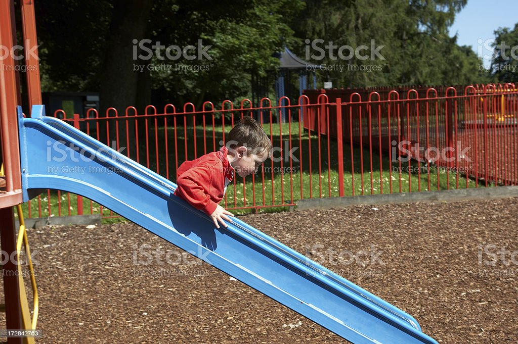Young boy on park slide stock photo