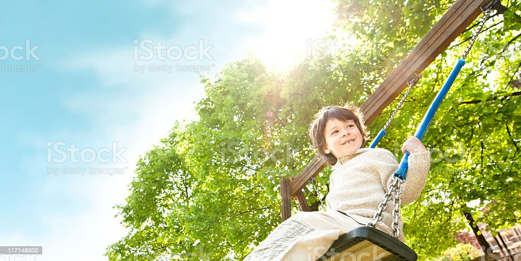 Young boy on swing in outdoor playground stock photo