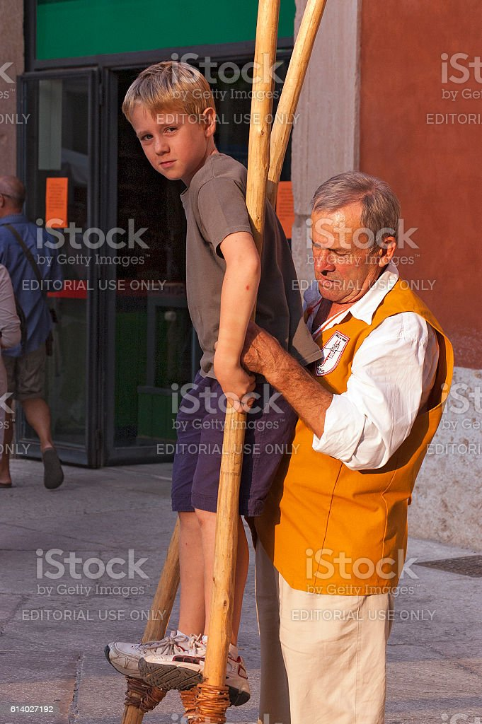 Young Boy on Wooden Stilts with Instructor stock photo