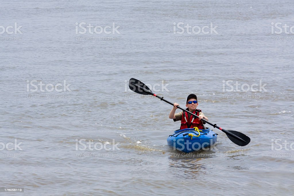 Young Boy Paddles Kayak on the water royalty-free stock photo