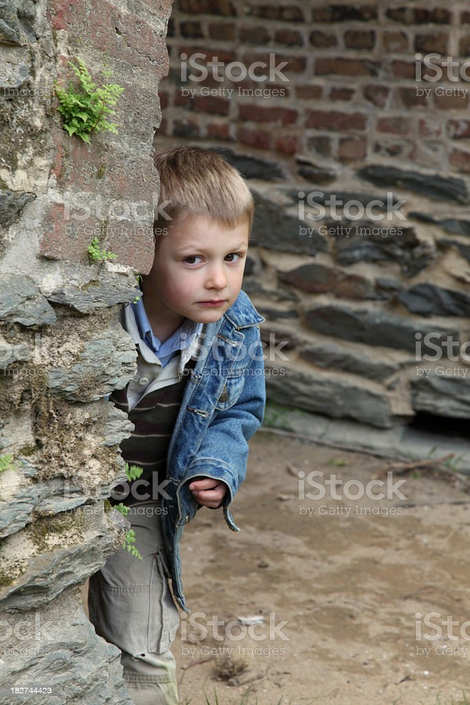 Young boy peeks around corner of old brick wall stock photo