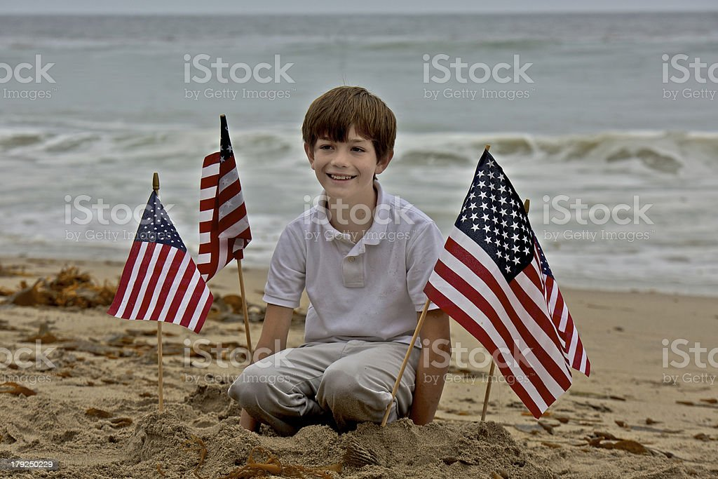 Young Boy Plants American Flags in Sand royalty-free stock photo