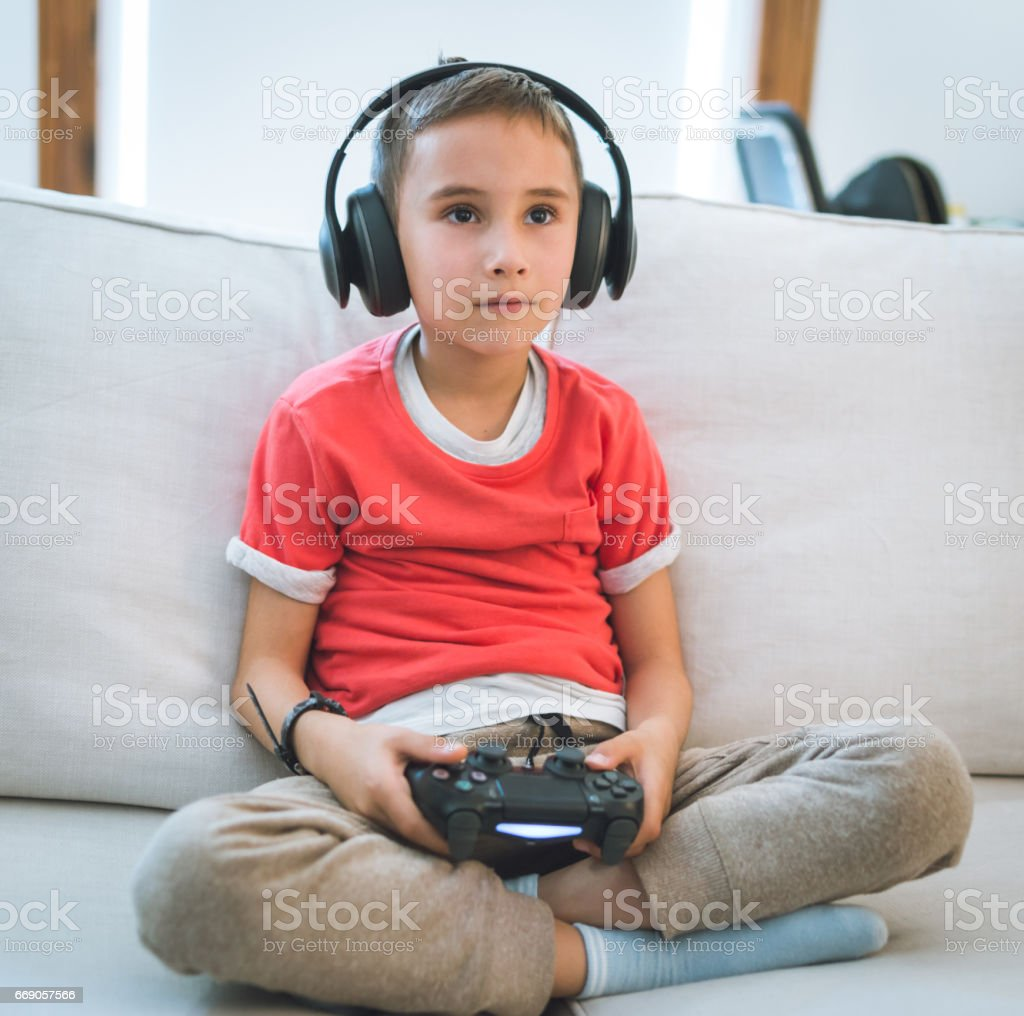 Young boy play the video game stock photo