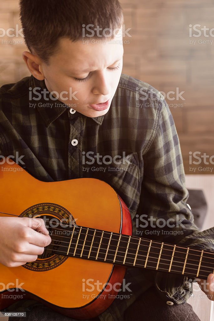 Young Boy Playing Acoustic Guitar in Living Room stock photo