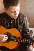 Young Boy Playing Acoustic Guitar in Living Room