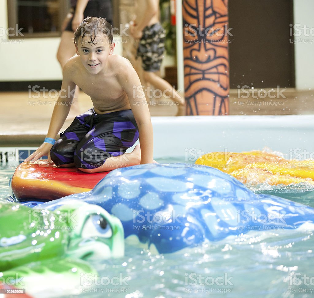 Young boy playing at the indoor water park stock photo