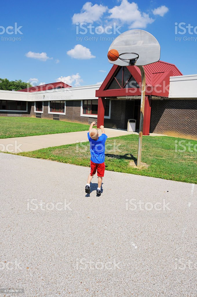 Young Boy Playing Basketball at School Playground stock photo